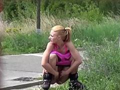 Mädchen auf Skates pinkelt am Strassenrand